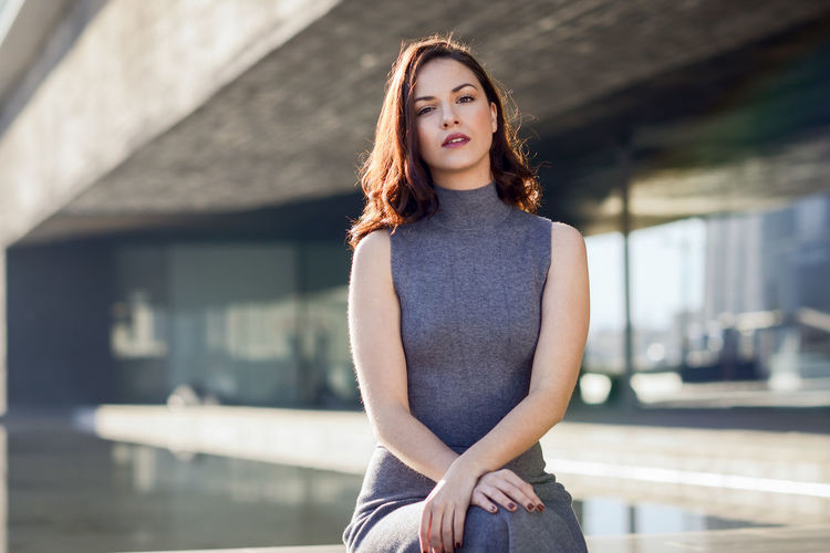 Portrait of young woman sitting outside modern building