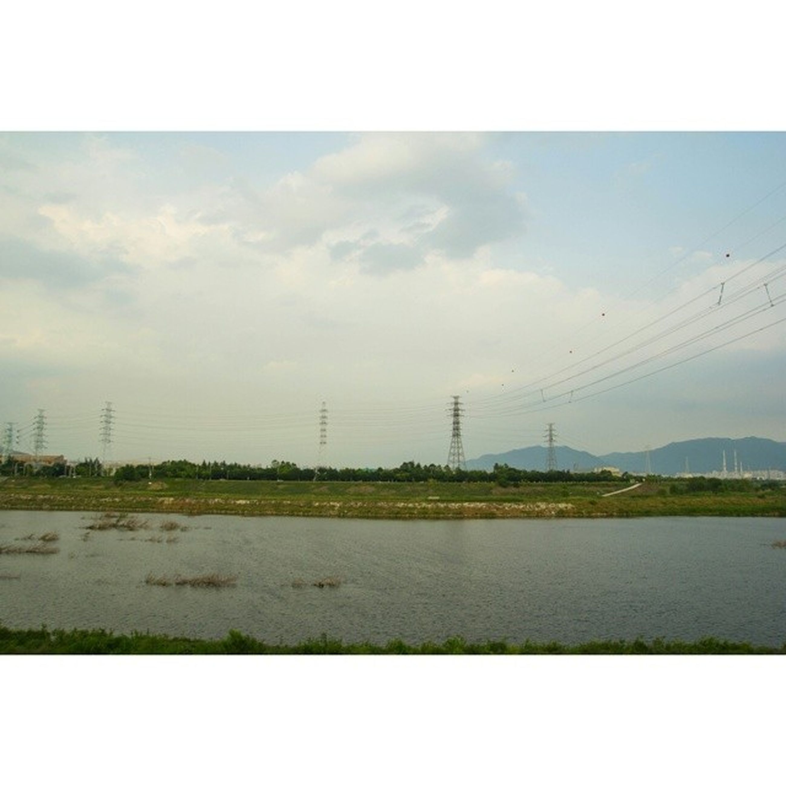 transfer print, electricity pylon, sky, power line, auto post production filter, field, grass, landscape, fuel and power generation, connection, power supply, electricity, tranquil scene, tranquility, cloud - sky, nature, water, scenics, cloud, rural scene