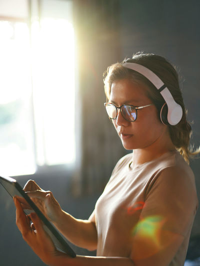 Mid adult woman using digital tablet wearing headphones