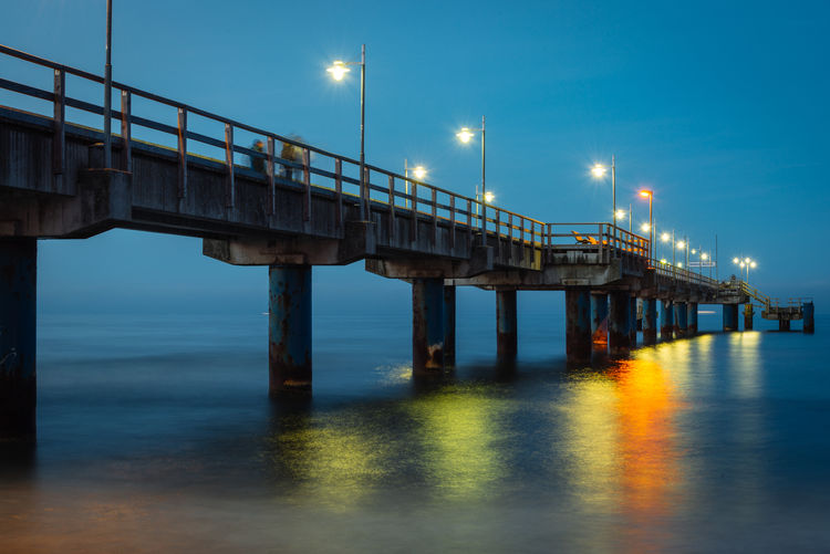 Low Angle View Of Illuminated Bridge Over Sea Against Sky At Dusk