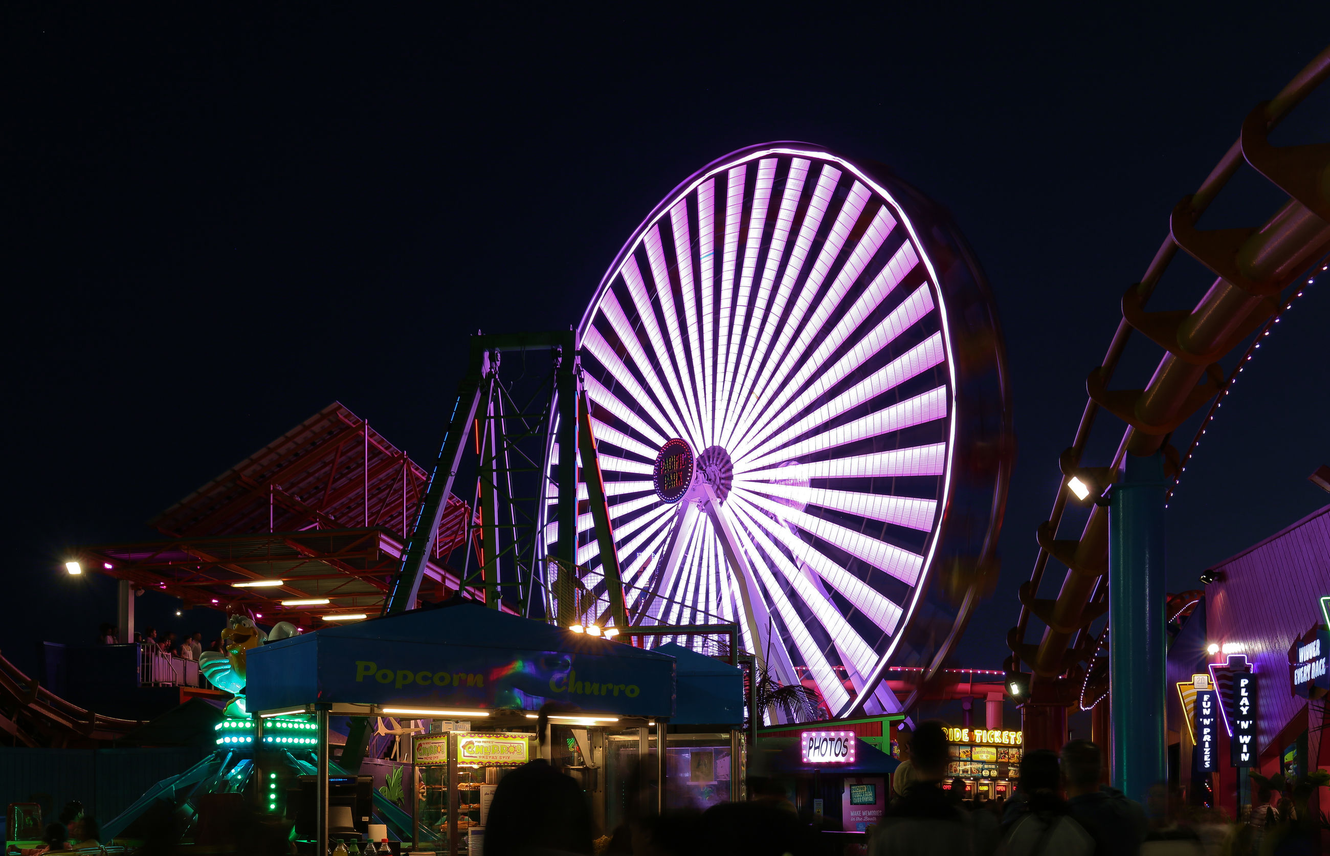 night, illuminated, arts culture and entertainment, leisure activity, large group of people, amusement park, built structure, women, nightlife, lifestyles, outdoors, real people, men, amusement park ride, crowd, multi colored, building exterior, ferris wheel, architecture, group of people, clear sky, sky, city, people