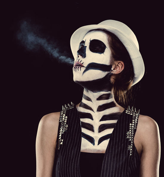 Woman with skeleton face art Black Background Day Of The Dead Halloween Horror Looking At Camera Make-up Makeup Skeleton Smoke Woman Body Arts Cigarette  Concept Conceptual Face Art One Person Skull Studio Shot Young Adult Young Women