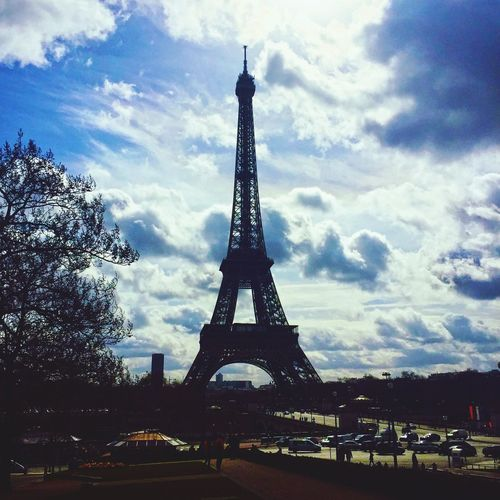 Silhouette of eiffel tower against cloudy sky
