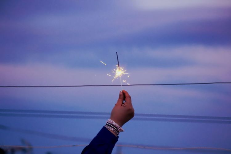 Close-Up Of Hand Holding Diwali Cracker Against The Sky