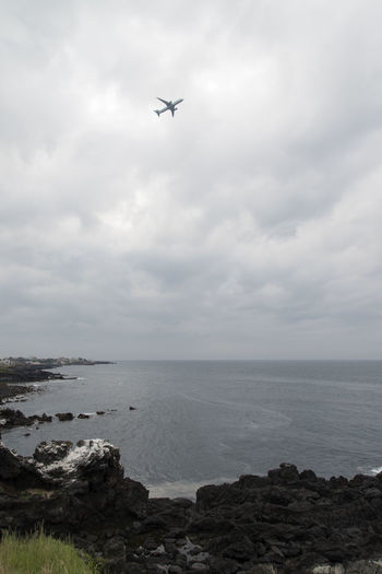 seaside view around Yongduam, dragon head rock in Jeju Island, South Korea Air Vehicle Airplane Cloud - Sky Cloudy Day Dragon Head Rock Flying Horizon Over Water JEJU ISLAND  Low Angle View Mid-air Nature No People Outdoors Rock - Object Sea Seaside Sky Transportation Water Yongduam