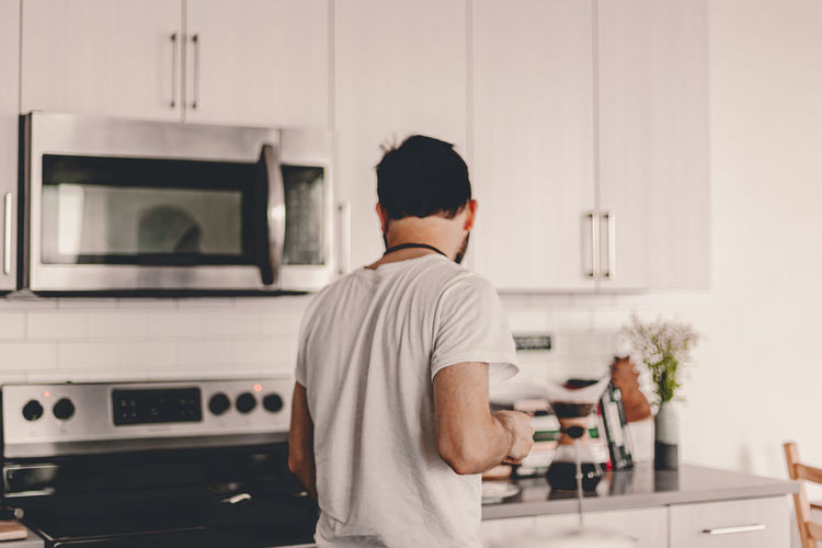 Rear view of man standing in kitchen
