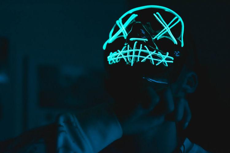 Close-up of man wearing glowing cap standing in darkroom