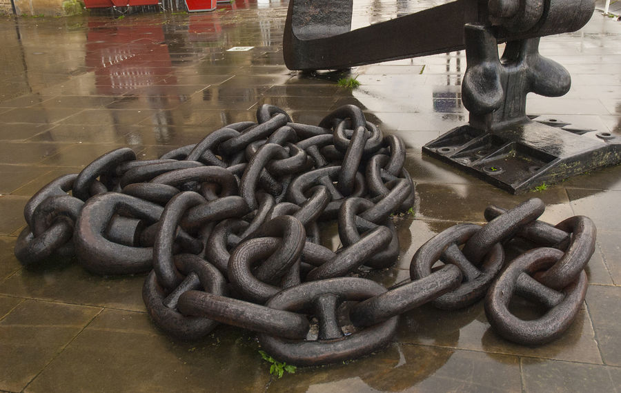 Abandoned anchor chain on a quayside neat to the Thames. Anchor Chain Chain Connection Day Daylight London Metal No People Outdoors Ship Part Strength Thames Water