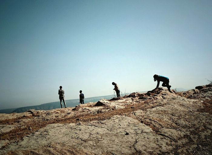 People standing on rock against clear sky