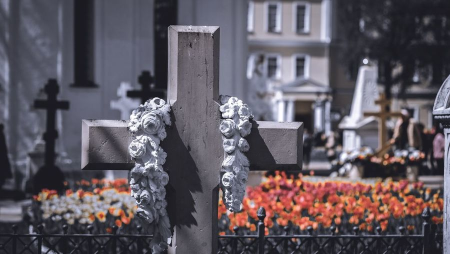 Close-up of cross in cemetery against building