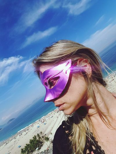 Woman wearing masquerade mask at beach against sky