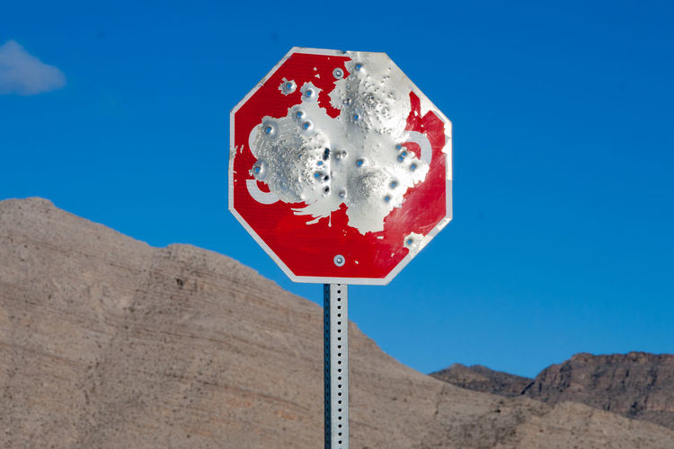 Low angle view of weathered red metallic road sign against sky