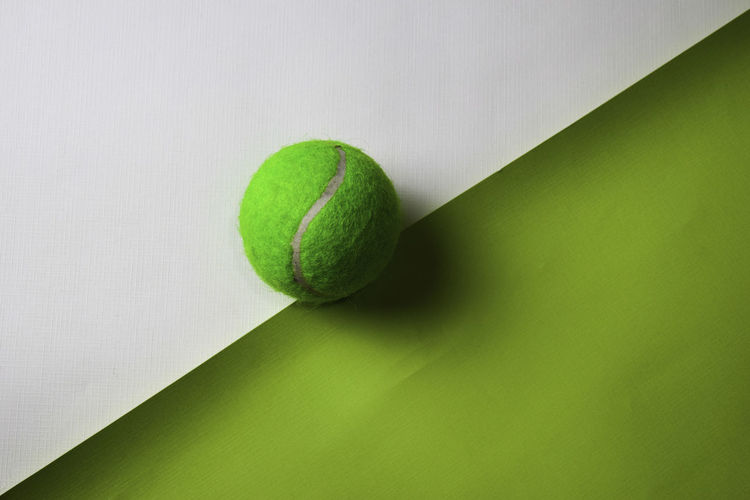 Directly above shot of tennis ball over two tone background
