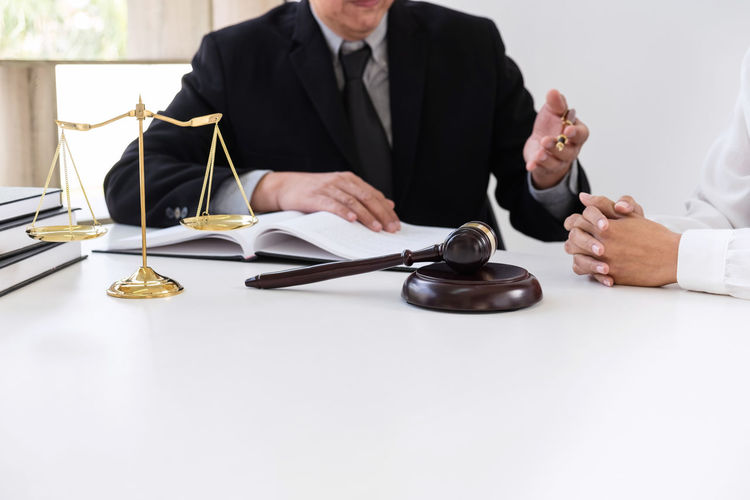 Midsection Of Male Lawyer Discussing With Customer At Desk