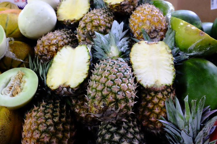 Close-up of pineapples and melons for sale