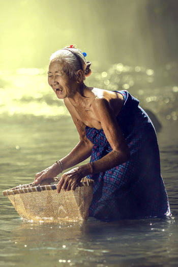Asian elderly woman happy finding fish in a streams. Old Woman Asian  Thailand People ASIA INDONESIA Women person Farmer Culture Portrait Chinese Thai Face Sad Female Senior Countryside Happy Background Smiling Smile Local Rural Traditional Cooking Rice Grandmother Elderly Mother Older  Beautiful Poor  Market Lady Lifestyle Wrinkled Praying Food Myanmar Vietnam White Village Floating Japan Rustic Grandma Korean Poverty