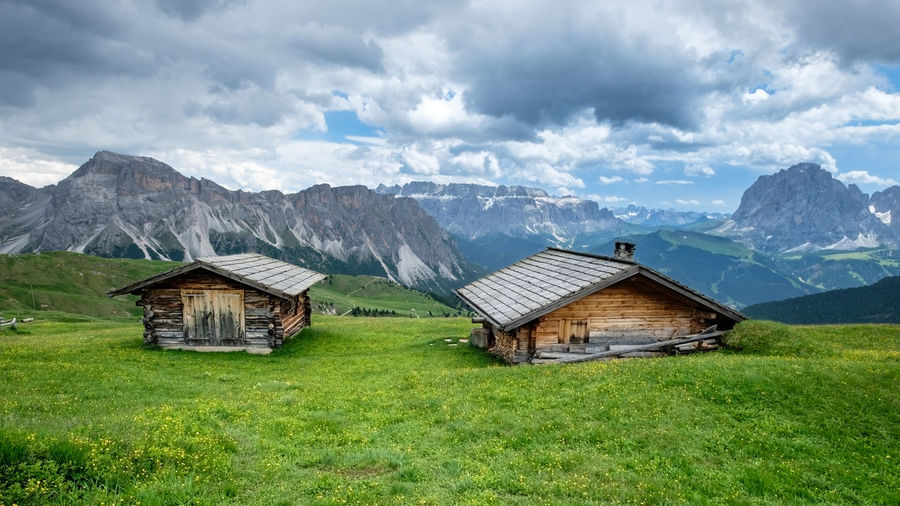 Green, empty beautiful summer ski huts and meadows, val gardena, dolomites, italy.