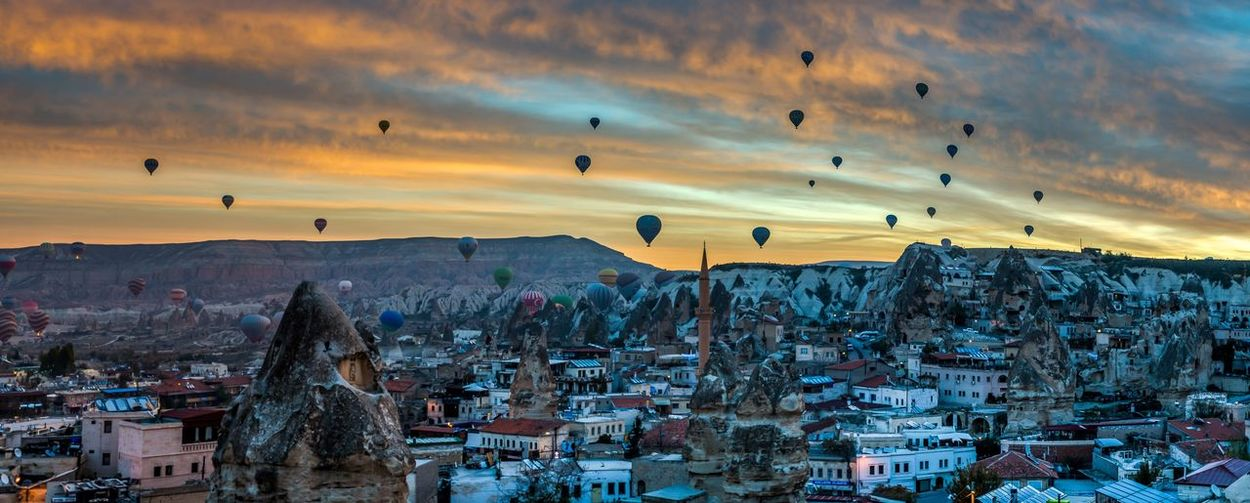 Hot air balloons over city against cloudy sky during sunset