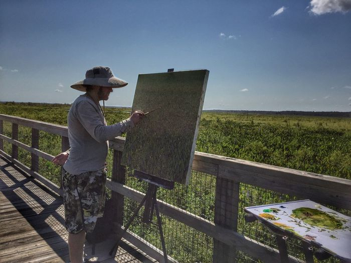 Side View Of Painter Painting By Landscape Against Sky