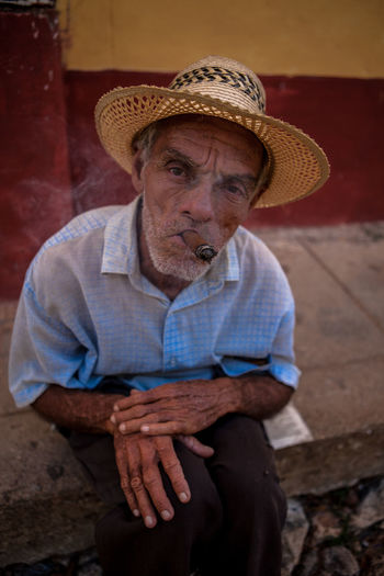 A cuban man poses for tourist' pictures. Cuba Cuban Man Old Man People Portrait Portrait Photography Sigar Smoke Strawhat Strawhatportraits Trinidad Trinidad, Cuba