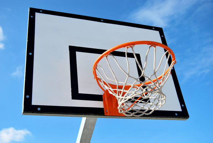 Basketball - Sport Basketball Hoop Blue Competition Day Directly Below Leisure Activity Leisure Games Low Angle View Making A Basket Motion Nature Net - Sports Equipment No People Orange Color Outdoors Scoring Sky Sport Taking A Shot - Sport Team Sport