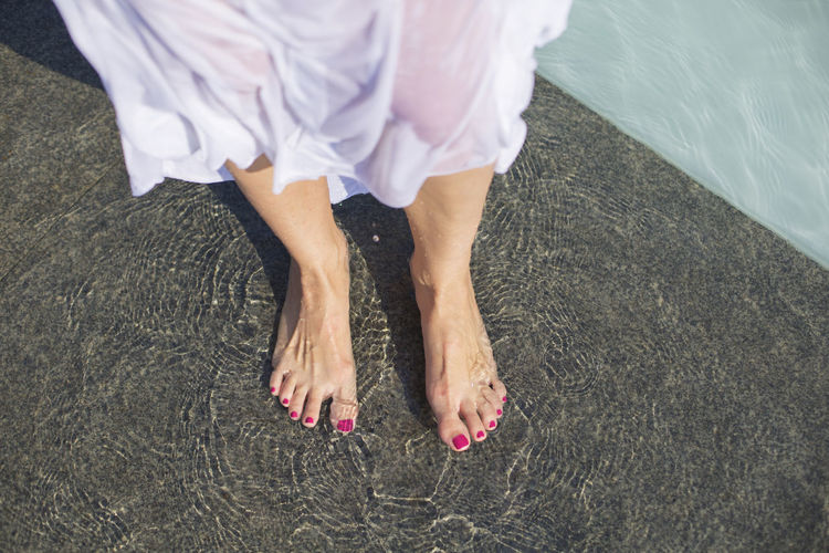 Low section of woman standing in water on tiled floor