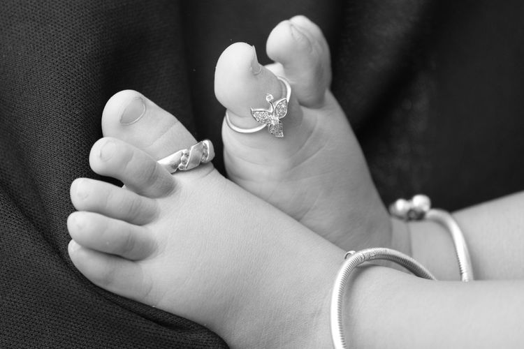 Low section of girl wearing rings and anklet