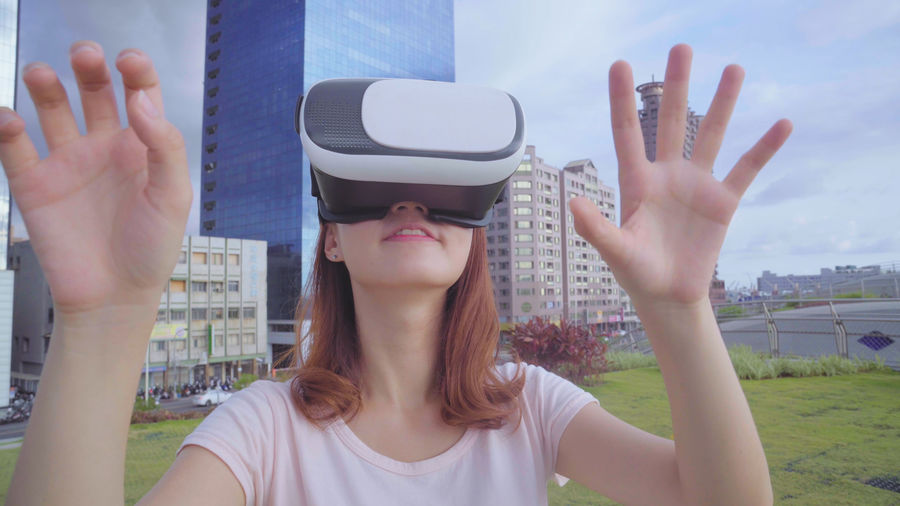 Beautiful woman using virtual reality simulator while standing against buildings in city