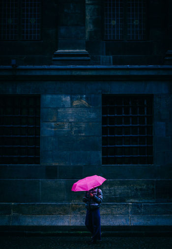 Woman standing on wet umbrella during rainy season
