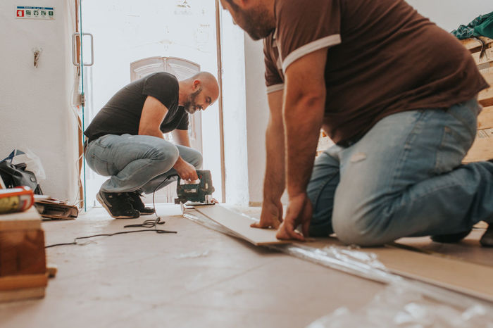 Construction Home Improvement Improvement Teamwork Carpenter Casual Clothing Concentration Cooperation Craftsperson Expertise Full Length Home Improvement Home Interior Indoors  Kneeling Manual Worker Occupation Small Business Standing Teamwork Two People Wood - Material Working Modern Workplace Culture