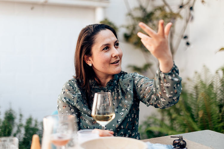 Woman sitting speaks cheerfully raising her arm and gesturing with her hand to reinforce her speech
