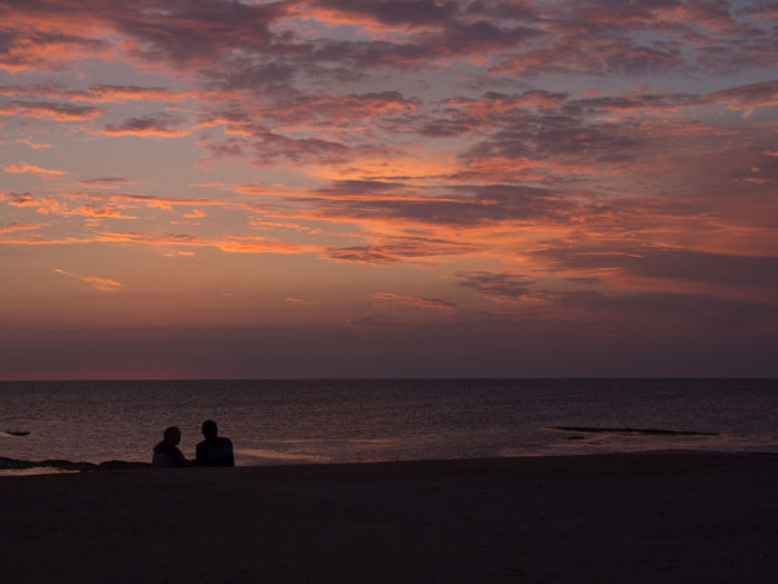 Silhouette couple sitting on beach against sky during sunset