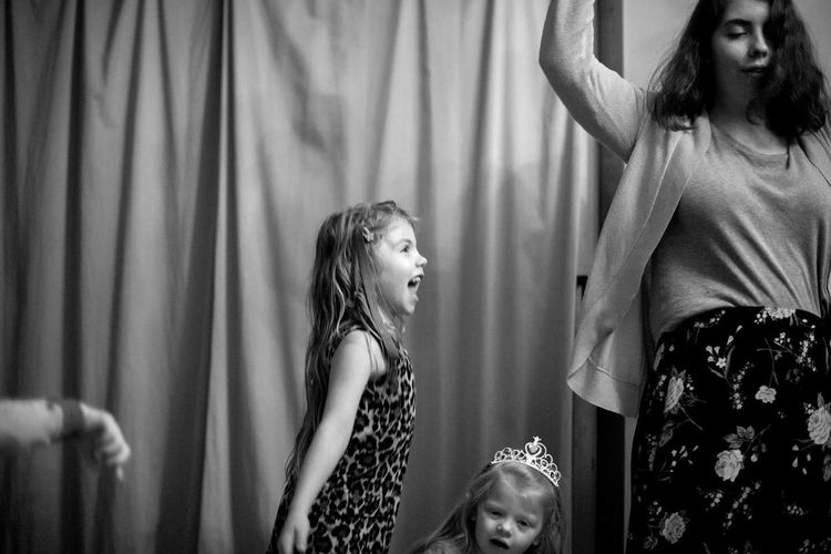 Mother With Happy Daughters Dancing At Home