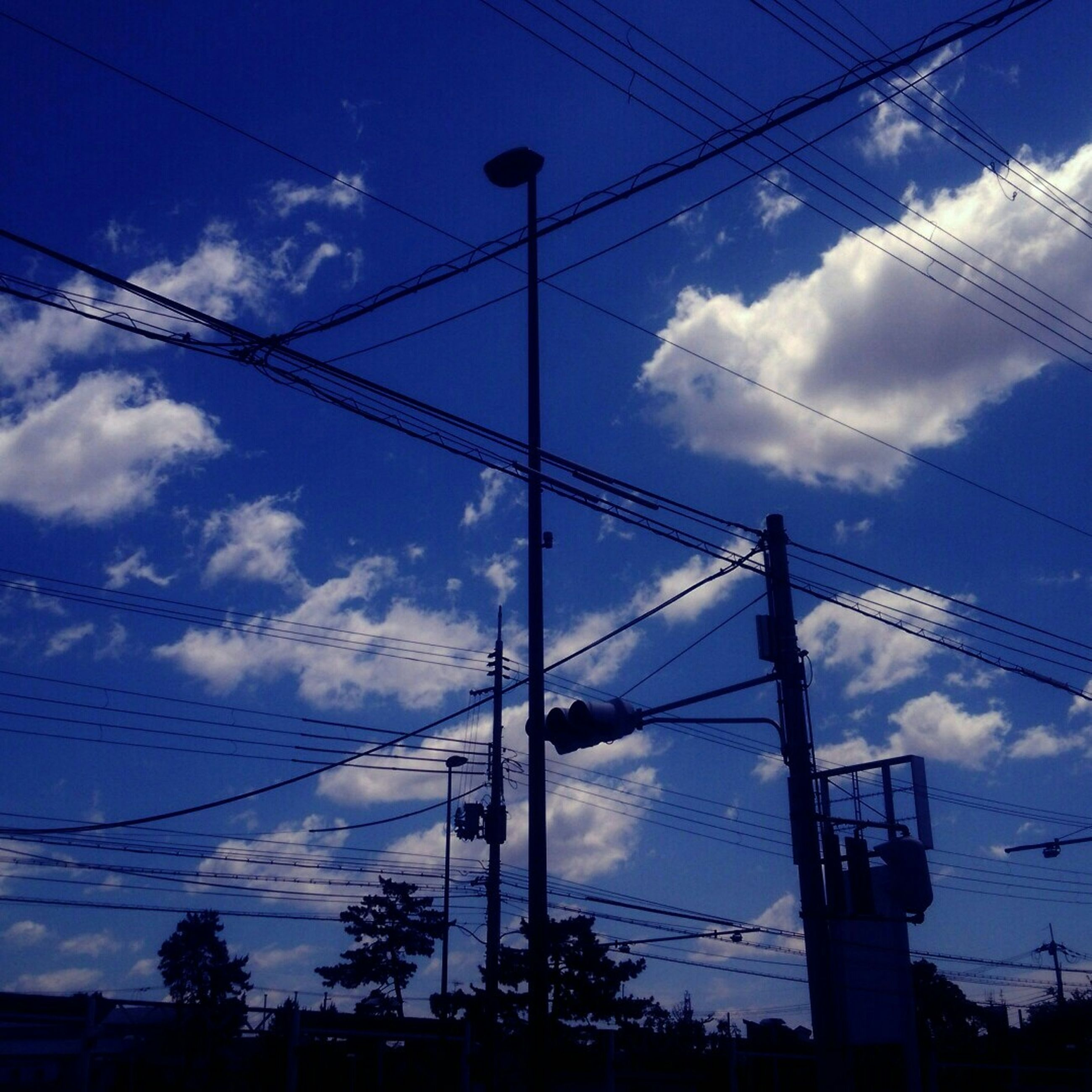 power line, electricity pylon, power supply, low angle view, sky, electricity, cable, connection, cloud - sky, blue, fuel and power generation, power cable, technology, cloud, cloudy, silhouette, built structure, architecture, no people, outdoors