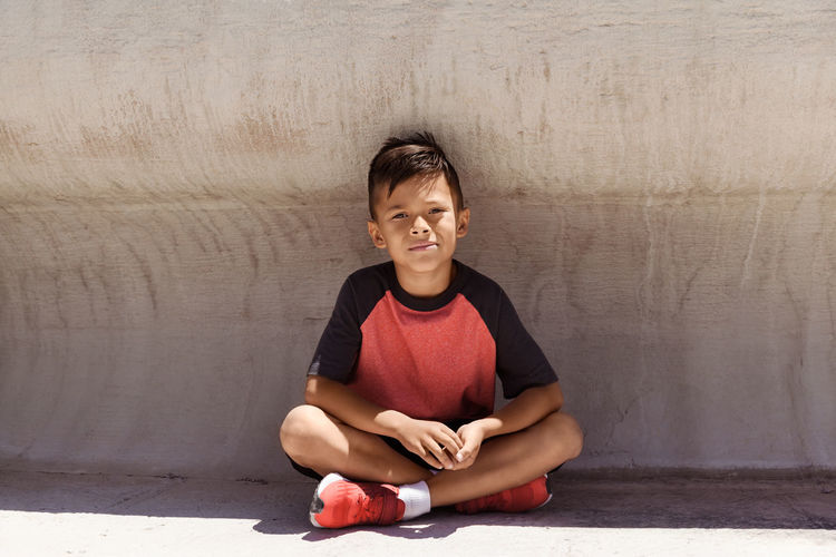 Portrait Of A Boy Sitting On A Walkway, Street Photography One Person Child Sitting Portrait Walkway Front View Childhood Day Casual Clothing Kid Sunlight Boy Outdoors Street Horizontal Candid People Innocence Smiling Lifestyles Millenials Looking At Camera Cross-legged Active Shadow