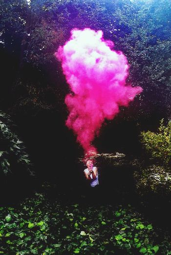 Woman holding pink distress flare in forest