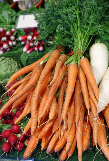 Fresh carrot bunches with green top on retail market stall Vegetable Food And Drink Food Root Vegetable Carrot Healthy Eating Freshness Market Large Group Of Objects Market Stall Orange Color For Sale Raw Food High Angle View Day Green Color Organic Retail Display Ripe Fresh New Harvest Organic Food Vegetarian Food Retail  17.62°