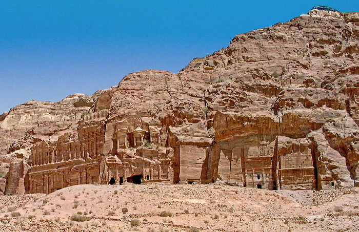 Royal rock tombs - Petra, Jordan Petra (Arabic: البتراء, Al-Batrāʾ; Ancient Greek: Πέτρα), originally known as Raqmu (Nabataean Arabic: الرقيم), is a historical and archaeological city in southern Jordan. Petra lies on the slope of Jabal Al-Madbah in a basin among the mountains which form the eastern flank of Arabah valley that run from the Dead Sea to the Gulf of Aqaba. Established possibly as early as the 4th century BC as the capital city of the Nabataean Kingdom. The Nabataeans were nomadic Arabs who invested in Petra's proximity to the trade routes by establishing it as a major regional trading hub. In AD 106 Petra was annexed by the Roman empire. Rome's diversion of the caravan trade and some devastating earthquakes in subsequent centuries put the city into decline. Nabataean Kingdom Petra Jordan Ancient Ancient Architecture Ancient Civilization Archaeology Architecture Arid Climate Beauty In Nature Blue Built Structure Clear Sky Day Desert History Low Angle View Mountain Nature No People Old Ruin Outdoors Rock - Object Royal Tombs Sky Travel Destinations