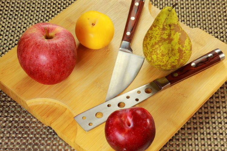 High angle view of fruits and knives on cutting board