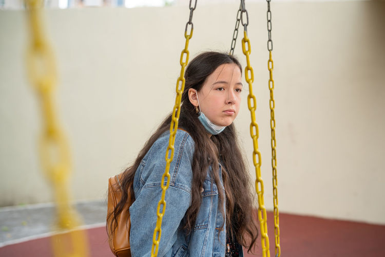 Portrait of girl standing against yellow wall