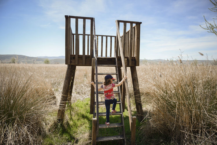 Little girl climbing to a wooden observation tower in a wetland in Padul, Granada, Andalusia, Spain Arms Raised Casual Clothing Child Childhood Day Field Full Length Grass Human Arm Innocence Land Landscape Leisure Activity Lifestyles Nature Non-urban Scene One Person Outdoors Plant Real People Sky Standing