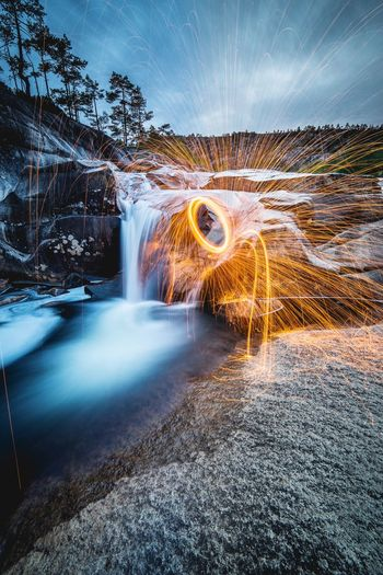Light trails by waterfall against sky