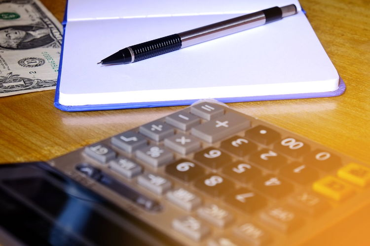 High angle view of calculator with book and pen on table