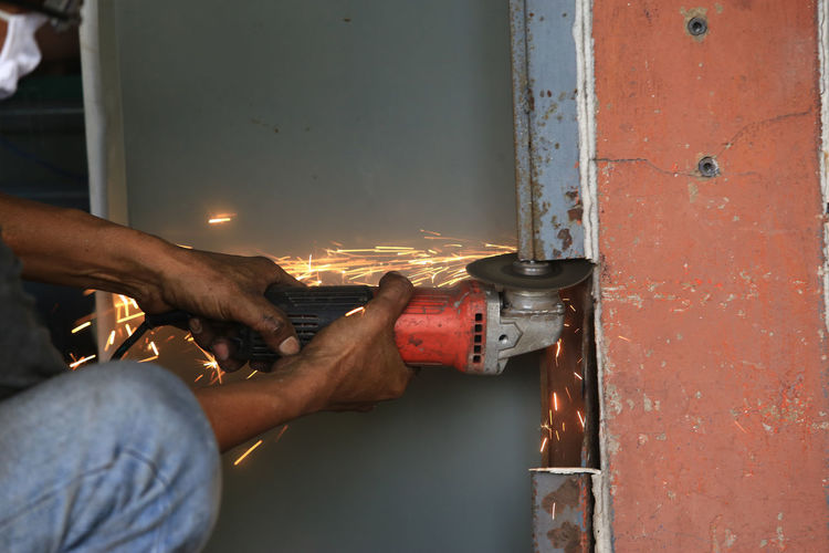Midsection of worker cutting metal