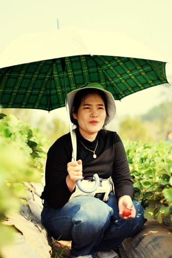 Woman holding umbrella while sitting by plants