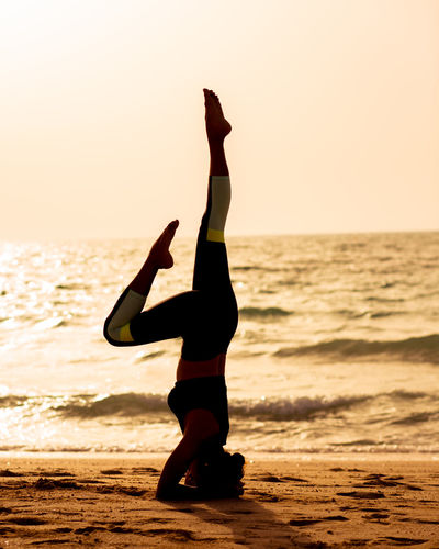 Full length of woman practicing headstand at beach against clear sky during sunset