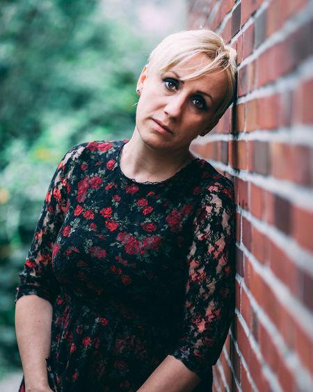 Portrait of beautiful woman standing by brick wall