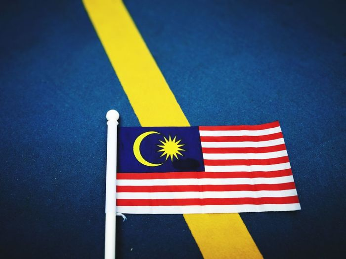 The flag of Malaysia on a yellow stripe and dark blue background. EyeEm Blue Independence Flag Yellow Malaysia Patriotism Democracy Independence Day Symbol Patriotic Malaysian Flag Striped Close-up Symbolism Malay Citizenship Malaysia Truly Asia Malaysian Cultures EyeEm Best Shots Merdeka National Flag Malaysia Flag National Icon Politics And Government EyeEm Selects No People High Angle View Shape Still Life Indoors  Star Shape Pride Table White Color Red