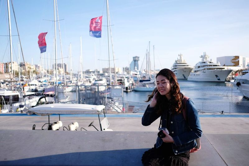 Young woman in harbor against sky