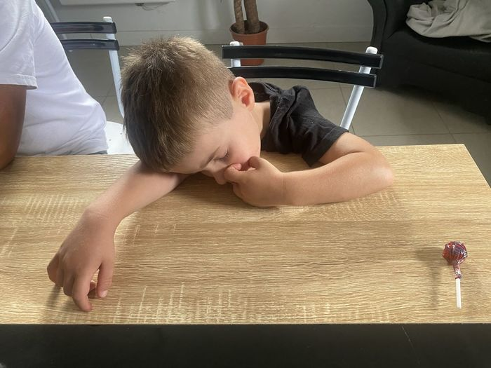 High angle view of boy lying on table at home